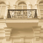 Wrought-iron balcon on the light side of the building. Toned