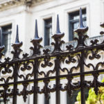 Old ornamental wrought iron fence with spiked tops in front of stone building